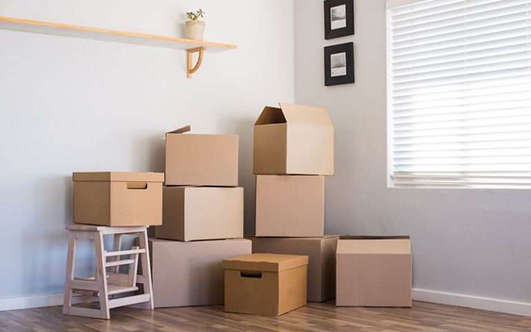 Moving boxes inside of an apartment room
