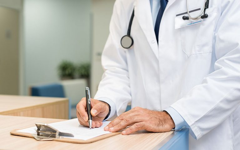 Doctor writing information on a clipboard